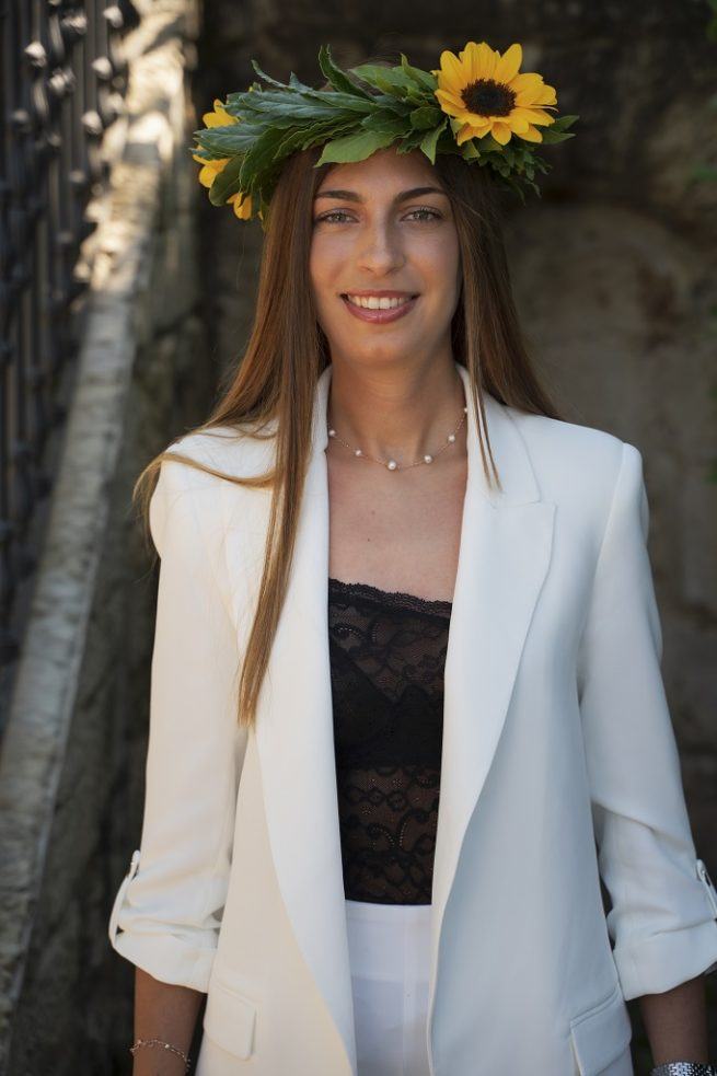 Foto dal fronte di una corona d'alloro con girasoli indossata da una ragazza