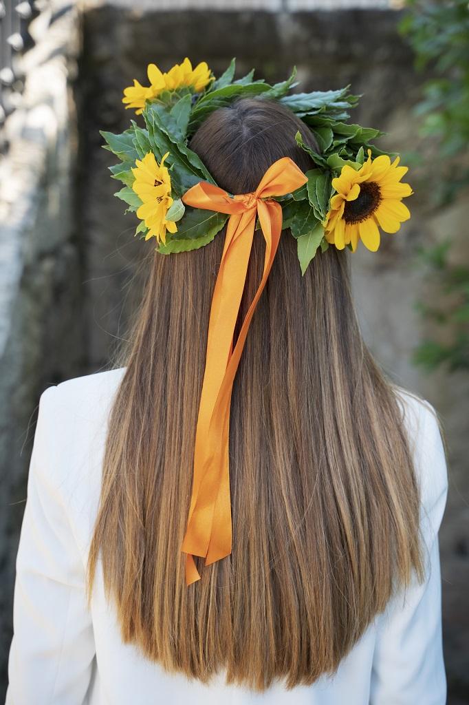 Retro di una corona d'alloro con girasoli indossata da una ragazza